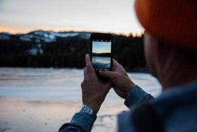 Man taking picture of frozen lake