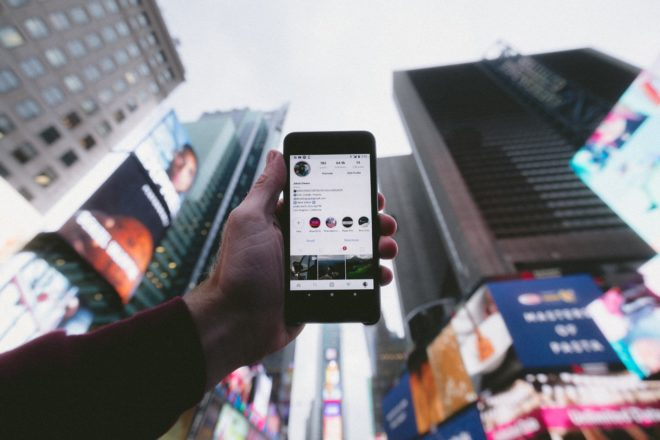 holding phone facing skyscrapers